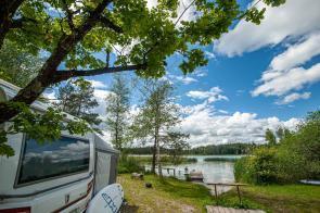 Blick vom Campingplatz auf den See mit Bootssteg, SUP und blauem Himmel