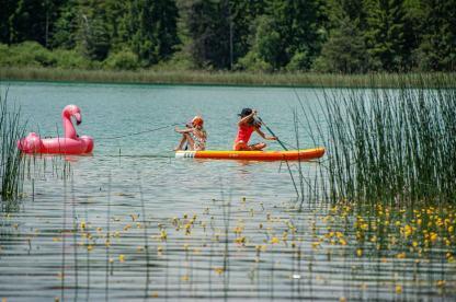 Flamingo Badetier mit zwei Mädchen von einem SUP gezogen beim Camping