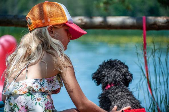 Kind und Hund gucken beim Camping auf einen See