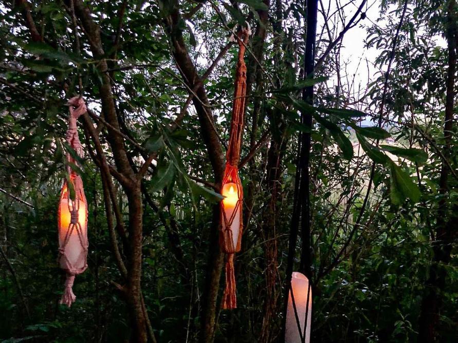 Leuchtende Kerzen im Baum mit Makramee Blumenampeln