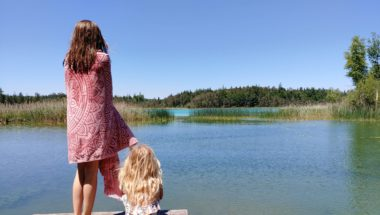 zwei Kinder auf einem Steg am See gucken auf das Wasser beim Anbaden