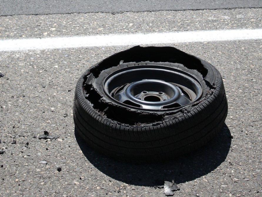 kaputter Wohnwagen Reifen mit Felge liegt auf der Straße