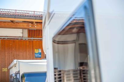 TÜV Süd Schild am Gebäude einer Caravan Werkstatt - Dichtigkeitsprüfung am Wohnwagen