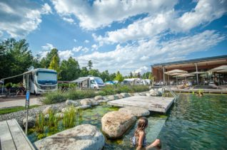 Natur Badesee mit Camping Stellplätzen und Freizeitfahrzeugen sowie der Außenterasse vom Restaurant des Campingplatzes Montiggl - Camping in Apulien