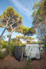 Wohnwagen von vorne auf dem Stellplatz mit Bäumen und Sträuchern - Camping in Apulien