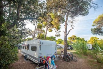 Wohnwagen von hinten auf dem Stellplatz mit Bäumen, Sträuchern, Handtüchern und Fahrrädern - Camping in Apulien