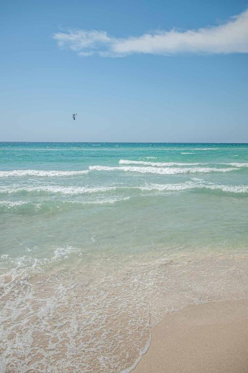 türkises Meer mit eißem Strand und Kiter - Camping in Apulien