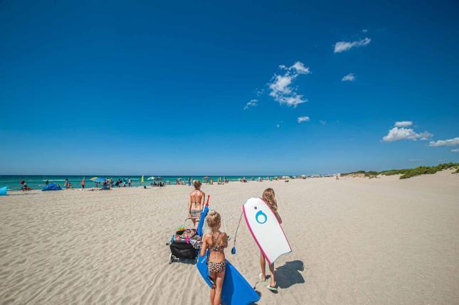 Famile auf dem Weg zum Strand mit Bodyboards - Camping in Apulien