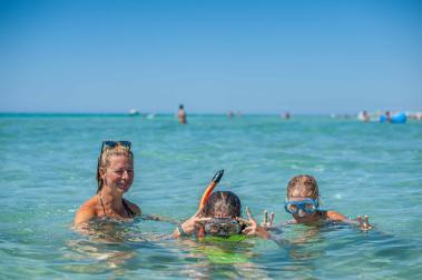 Familie im türkisen Wasser beim Schnorcheln - Camping in Apulien