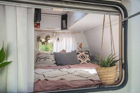 weiß renovierter Schlafbereich eines Wohnwagens durch das Seitenfenster - Boho Style