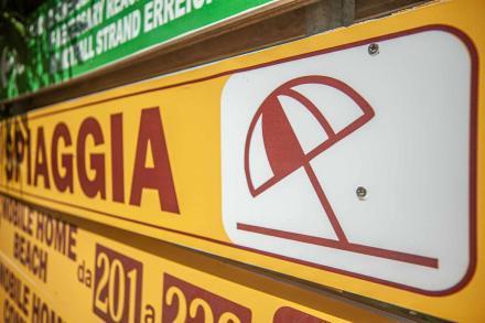 gelbes Hinweis Schild Spiaggia mit Sonnenschirm - Camping in Apulien