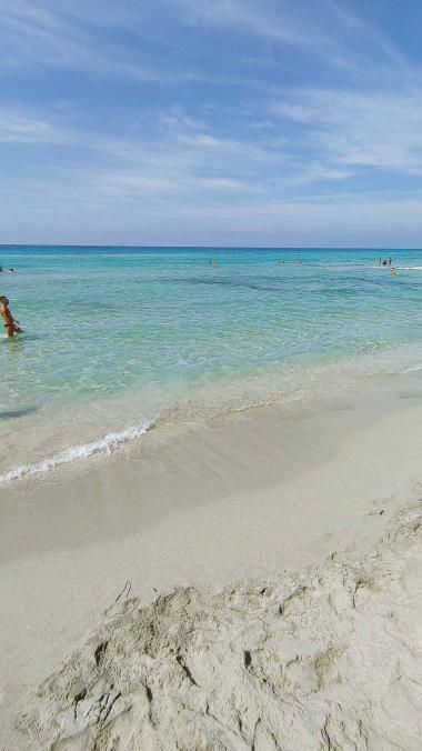 Mann geht durch klasklares türkises Wasser am Strand von Riva di Ugento - Camping in Apulien