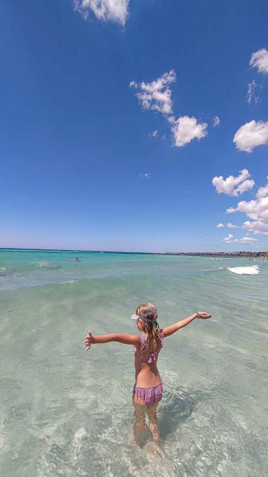 Kind mit Taucherbrille vor dem Sprung ins türkise Wasser - Camping in Apulien