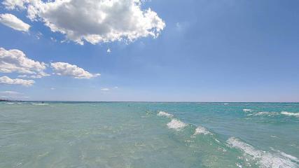 türkise Wasser Wolken und Sonnemit kleinen Wellen am Strand in Apulien - Camping in Apulien