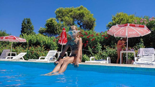 Kind sitz mit Taucherbrille auf dem Poolrand mit Ligestühlen und Sonnenschirmen im Hintergrund - Camping in Apulien
