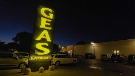 Nachtaufnahme mit beleuchtetem GEAS Supermarkt Schild in Apulien - Camping in Apulien