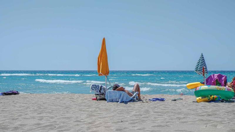 Liegestuhl mit Schirm und schlafendem Mann mit türkisem Meer
