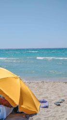 türkises Meer mit kleinen Wellen und einem orangen Sonnenschrim am Strand - Camping in Apulien