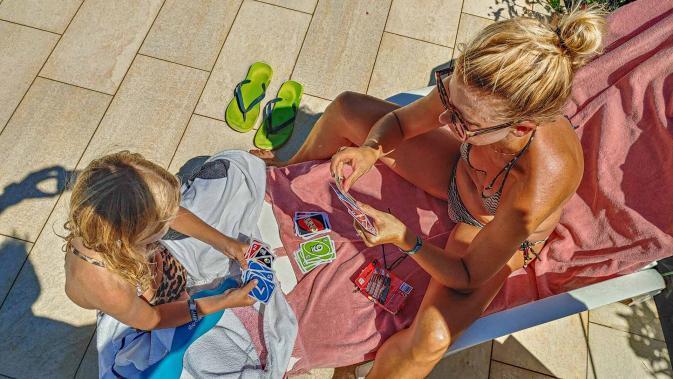 Mutter und Kind spielen ein Kartenspiel im Urlaub auf der Sonnenliege - Camping in Apulien