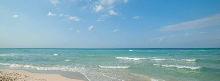 Blick auf das türkise Meer mit Wellen und Sonne in Apulien