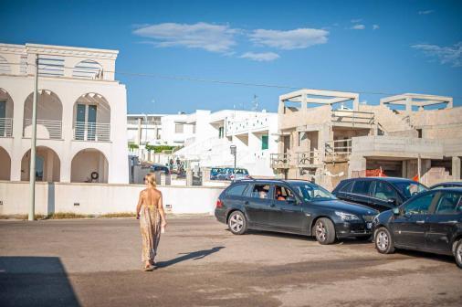 Parkplatz mit Häuserreien am Meer in Apulien