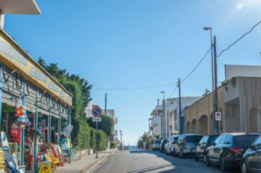 Straße zum Strand in Apulien mit Auos und Badesachen Geschäft