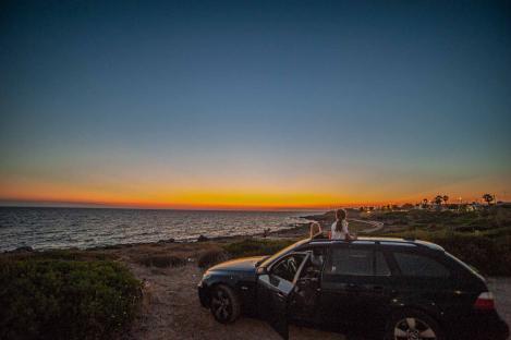 geparktes Auto am Strand auf einer Klippe mit Sonnenuntergang - Hinterland von Salento