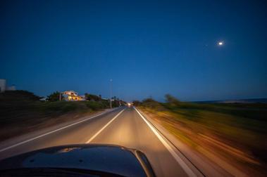 Fahrt mit dem Auto in der NAcht mit Schweinwerfern die die Starße beleuchten in Apulien