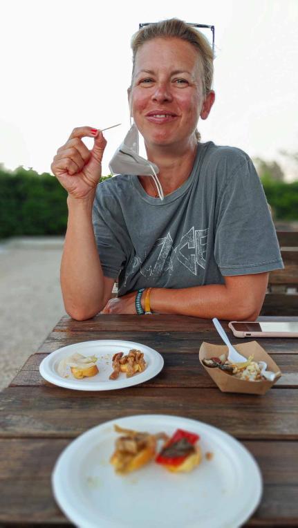 Frau sitzt beim Verköstigen von Antipasti bei iContadini