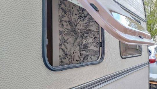 Caravan Makeover - Blick von außen durch das Wohnwagen Fenster in das Bad mit neuer Deko Tapete