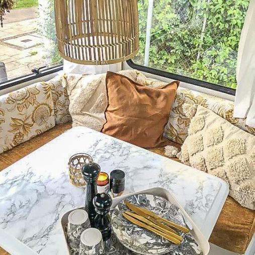 Caravan Makeover - neues Muster der Sitzpolster dekoriert mit Kissen und beklebtem Granit Klapptisch