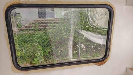 Caravan Makeover - Wasserschaden am alten Wohnwagen Fenster in den unteren Ecken hinter der Wandfolie