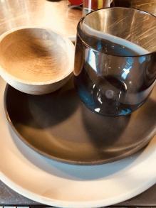 Camping Geschirr Tipps schwarze Teller und blaues Glas mit einer Mango Holz Schale