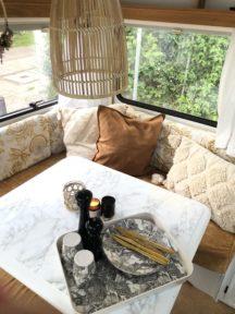 Camping Geschirr Tipps Tablett mit Tellern und goldenem Besteck im Wohnwagen
