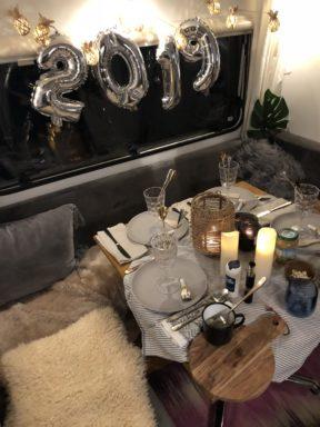 Camping Geschirr Tipps Im Wohnwagen gedeckter Tisch mit brennenden Kerzen und grauen Tellern