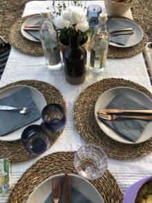 Camping Geschirr Tipps. schön gedeckter Tisch mit Bast Untersetzern und schwarzen Tellern