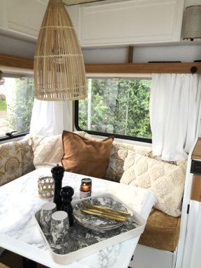 Wohnwagen und Caravan Makeover - Innenraum Dekoration - Kissen auf der Sitzbank - Marmortisch mit Folie bezogen - Gardinen und Korblampe