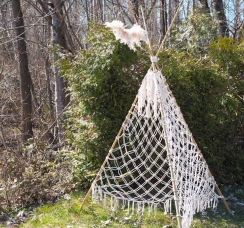 Makramee Tipi Zelt - Makramee Tipi Zelt auf grünem Rasen vor einer Hecke