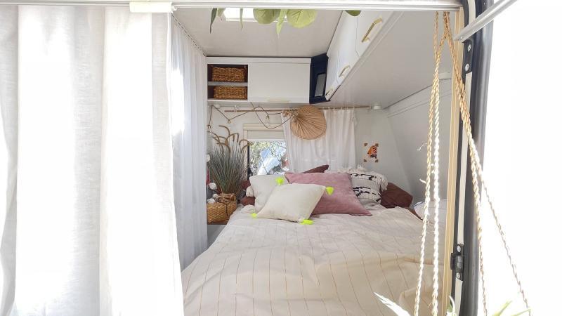 Wohnwagen Blick in das Schlafzimmer mit heller Bettwäsche und Kissen